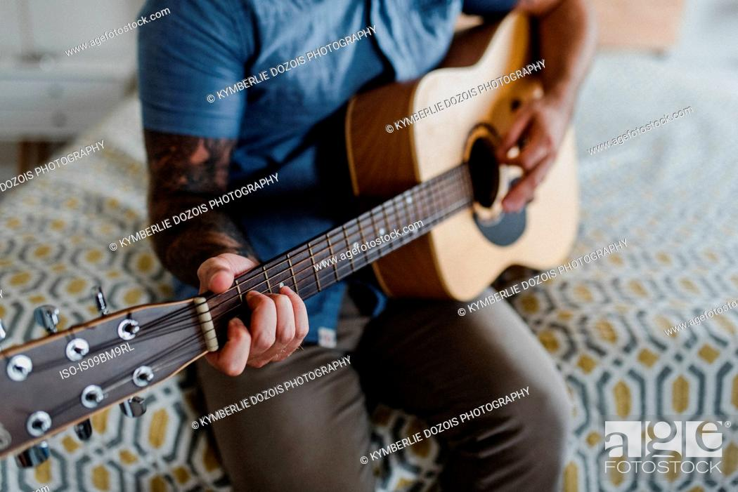 Imagen: Guitarist playing music on bed.