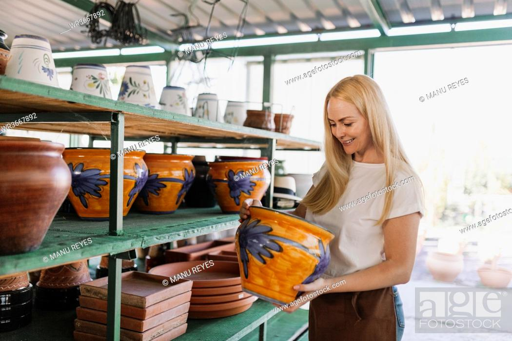 Stock Photo: Smiling female owner holding pottery while standing by shelf in workshop.