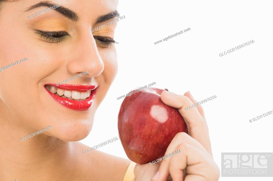 Imagen: Close-up of a woman holding a red apple and smiling.