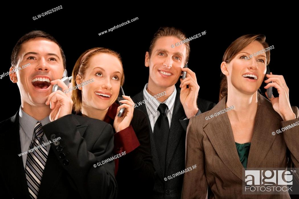 Stock Photo: Business executives talking on mobile phones and smiling.