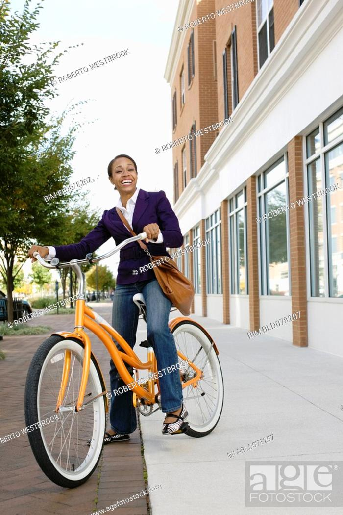 Stock Photo: African American woman riding bicycle.