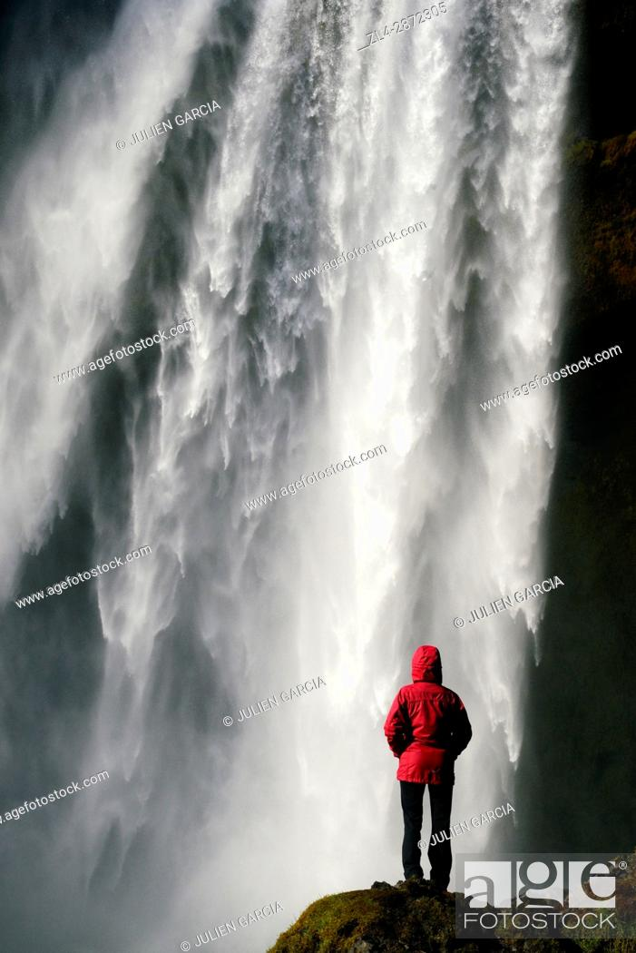 Stock Photo: Iceland, Sudurland region, woman in front of Skogafoss waterfall, Model Released.