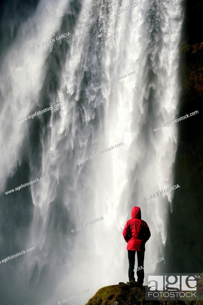 Photo de stock: Iceland, Sudurland region, woman in front of Skogafoss waterfall, Model Released.
