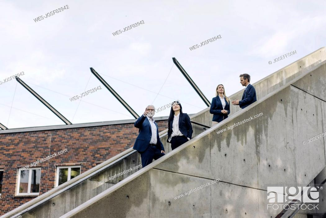 Stock Photo: Business people standing on exterior stair.