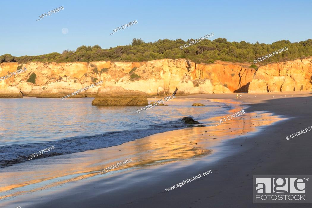 Stock Photo: The newly risen sun shines on cliffs and reflected on the beach of Praia do Vau Algarve Faro District Portimao Portugal Europe.
