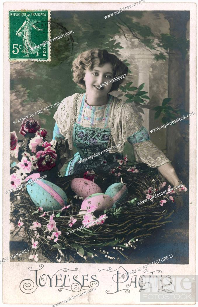 Stock Photo: A young woman in a garden with a basket full of large Easter eggs decorated in pink and blue.