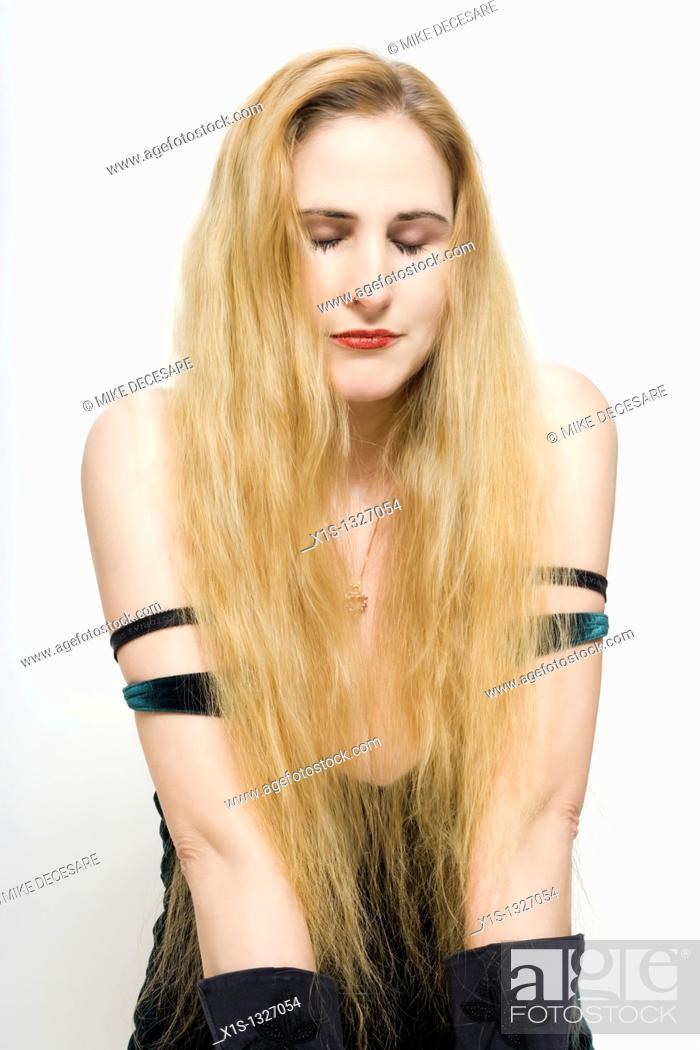 Stock Photo: A fair skinned woman with very long blond hair has her eyes closed as she kneels on the floor.