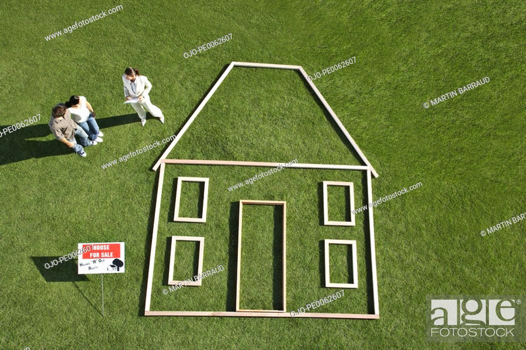 "Stock Photo: People standing near ""for sale"" sign and house outline."
