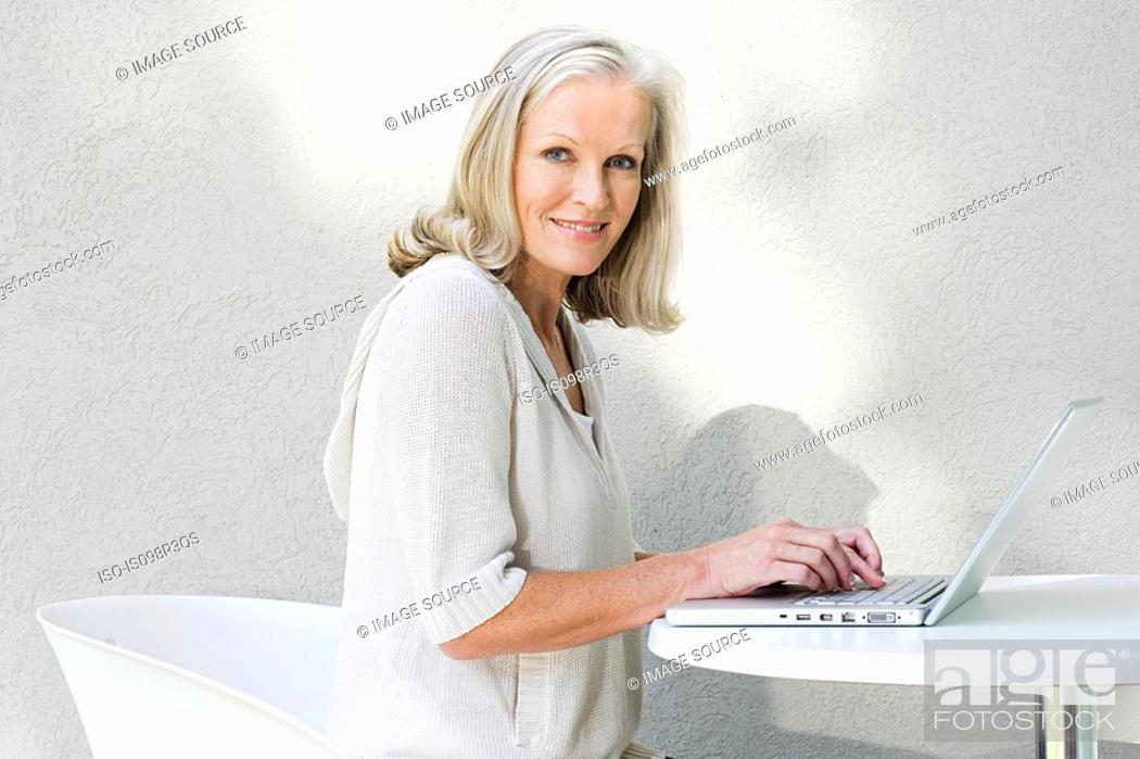 Stock Photo: Middle aged woman using laptop.