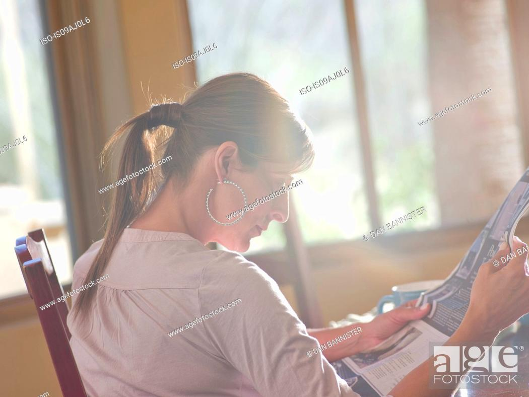 Stock Photo: Mature woman reading newspaper in dining room.