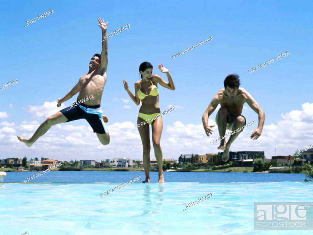Stock Photo: Young woman screaming as two young men jump into infinity pool.