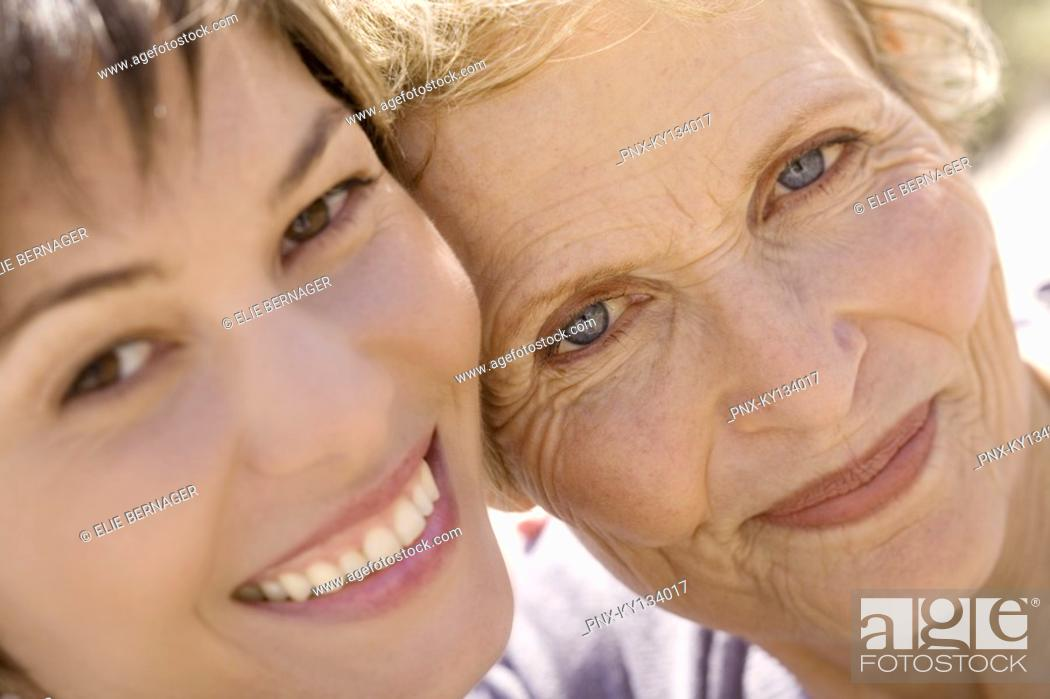 Stock Photo: Senior woman and adult daughter smiling for the camera, outdoors.