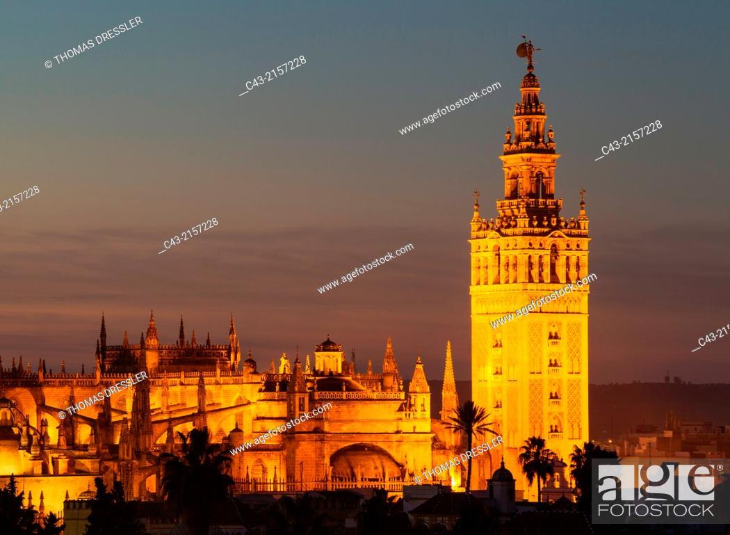 Stock Photo: The Moorish Giralda (1184-96) next to the Gothic Cathedral (1402-1506). Illuminated at dusk. Seville, Seville province, Andalusia, Spain.