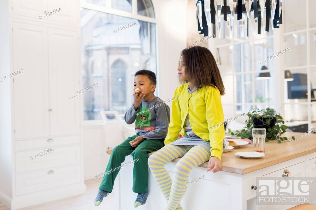Stock Photo: Brother and sister sitting on kitchen island.