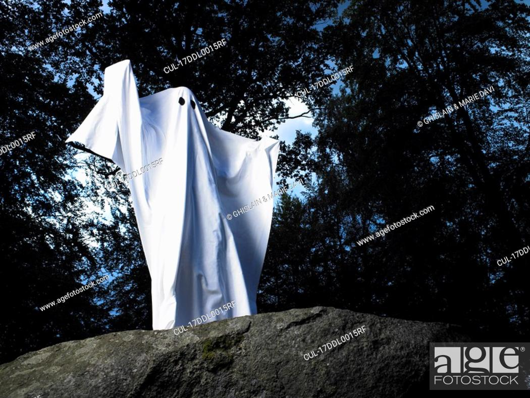 Stock Photo: Ghost made of sheets, standing on a rock.