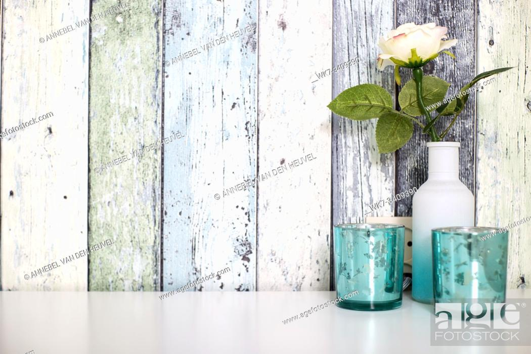 Stock Photo: one colorful flower in white vase against wood wall with blue decoration, space for text.