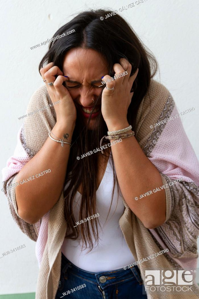 Stock Photo: Young girl making a scary gesture with her hands on her head.