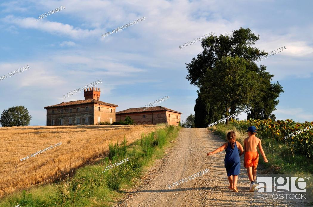 Stock Photo: Crespellano (Bologna, Italy): children walking along a road in the countryside, between the fields.