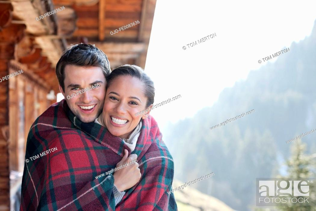 Stock Photo: Portrait of smiling couple wrapped in a blanket on cabin porch.