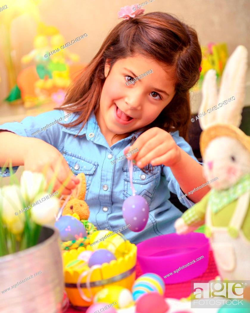 Stock Photo: Portrait of cute little girl decorating Easter eggs by different colors, having fun at home with bunny toy, drawing lesson in daycare.