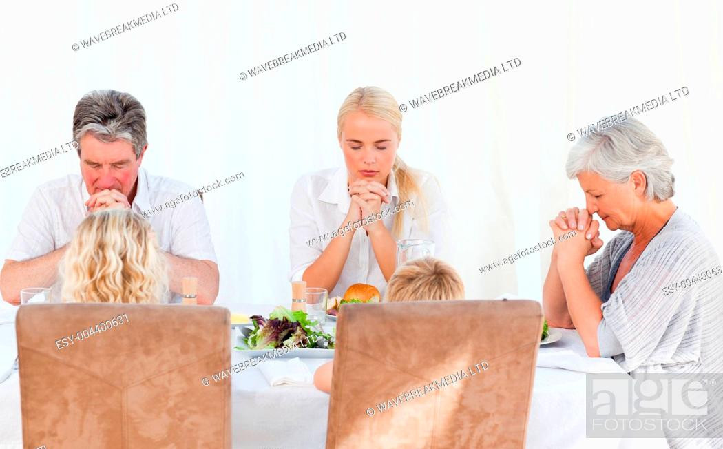 Stock Photo: Pretty family praying at the table.
