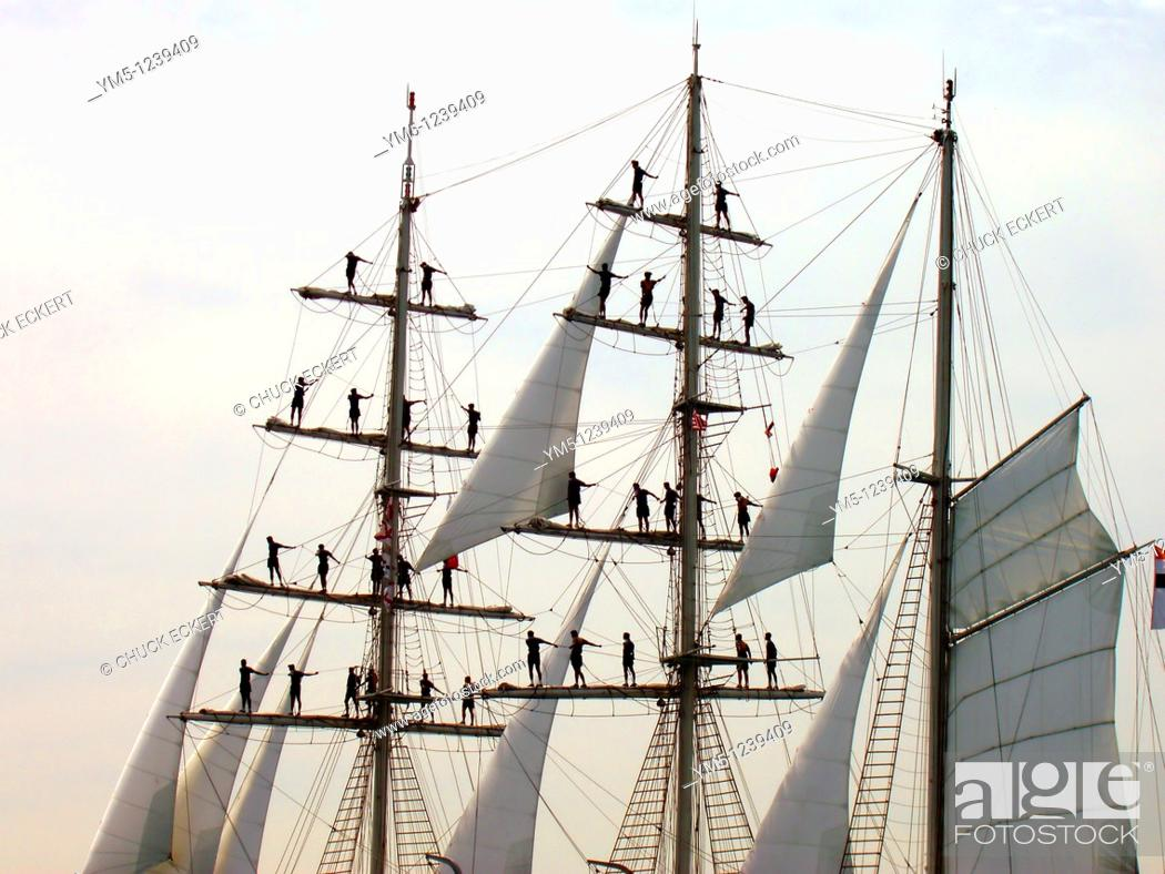 Stock Photo: Sailors atop Mast on Tall Ship. Concept might read Hang on...help is coming.