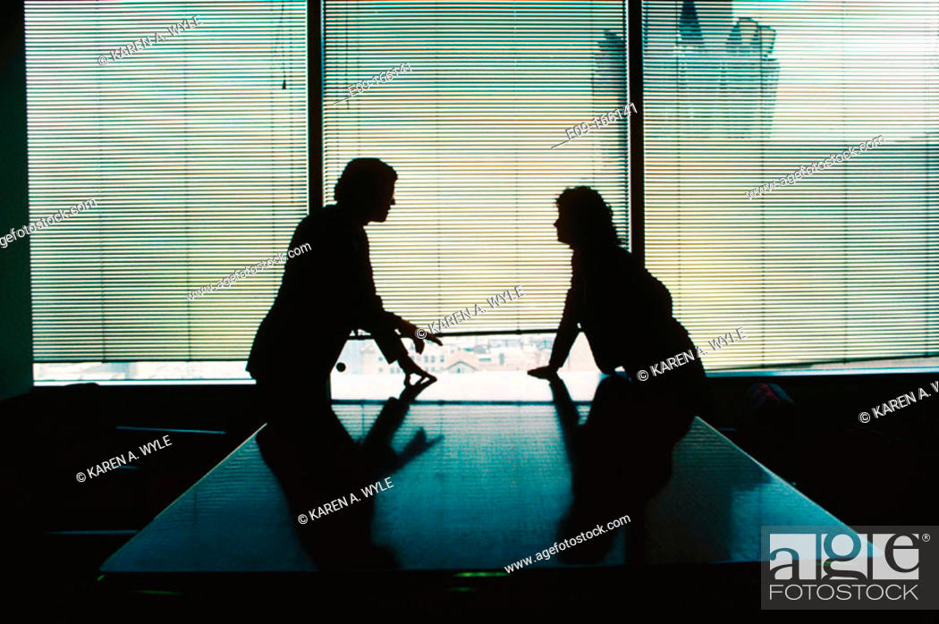 Stock Photo: Man and woman in business attire, silhouetted, leaning on polished table from opposite sides, confronting each other, in conference room, with window behind.