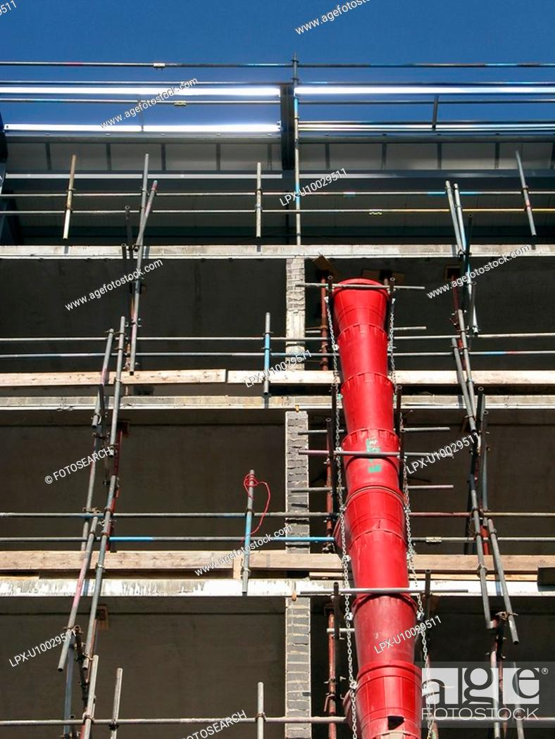 Stock Photo: View up scaffolding with red rubble chute prominent.
