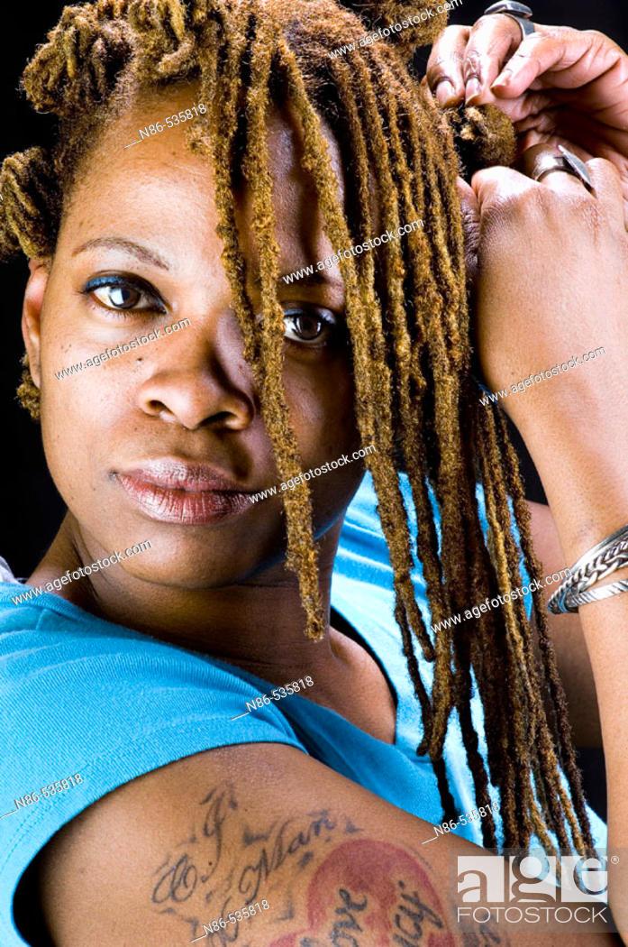 Stock Photo: Black woman braiding her hair.