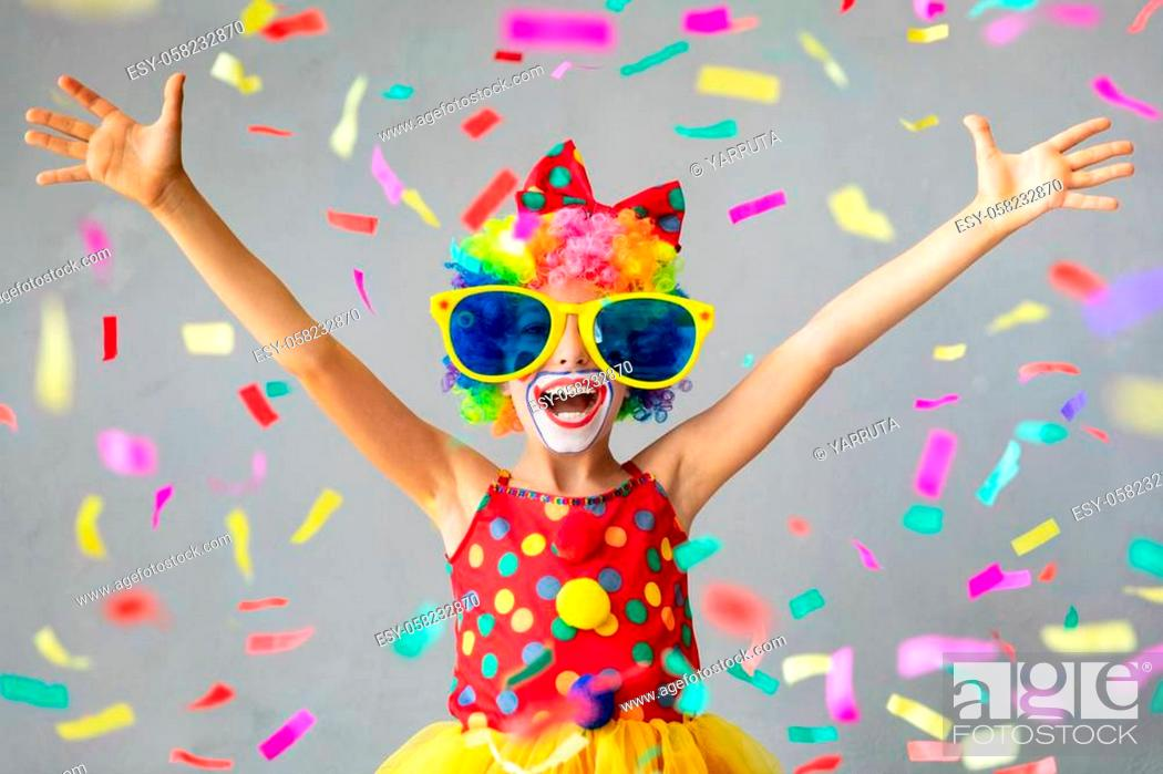 Stock Photo: Funny kid clown with pper confetti. Happy child playing at home. 1 April Fool's day concept.