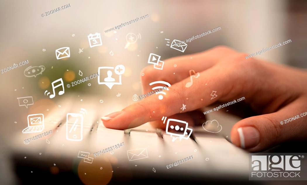 Stock Photo: Business woman hand typing on keyboard with drawn application icons around.