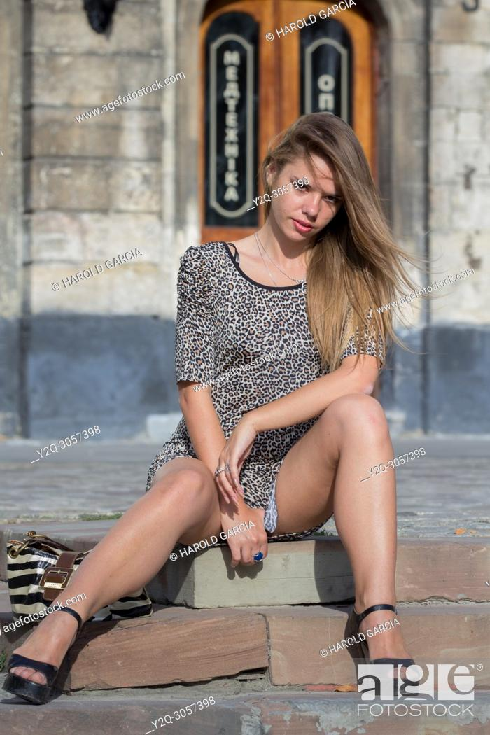 Imagen: Sexy Ukrainian woman wearing a leopard skin print dress posing seated on the floor for a photographic sequence in the ancient city of Lviv, Ukraine.