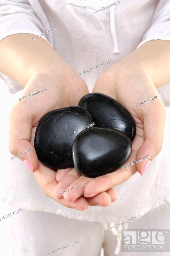 Stock Photo: Mid section view of a woman holding lastones.