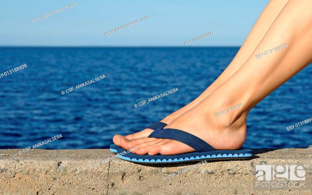 6cf0da00ebb84 Stock Photo - Female feet wearing blue flip-flops