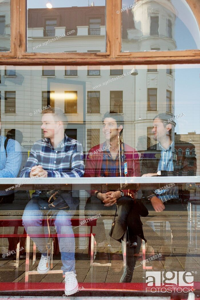 Stock Photo: Male friends sitting in cafe seen through glass window.