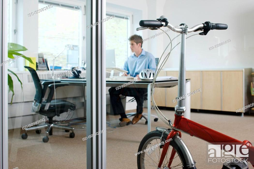 Stock Photo: Man in office with bike.