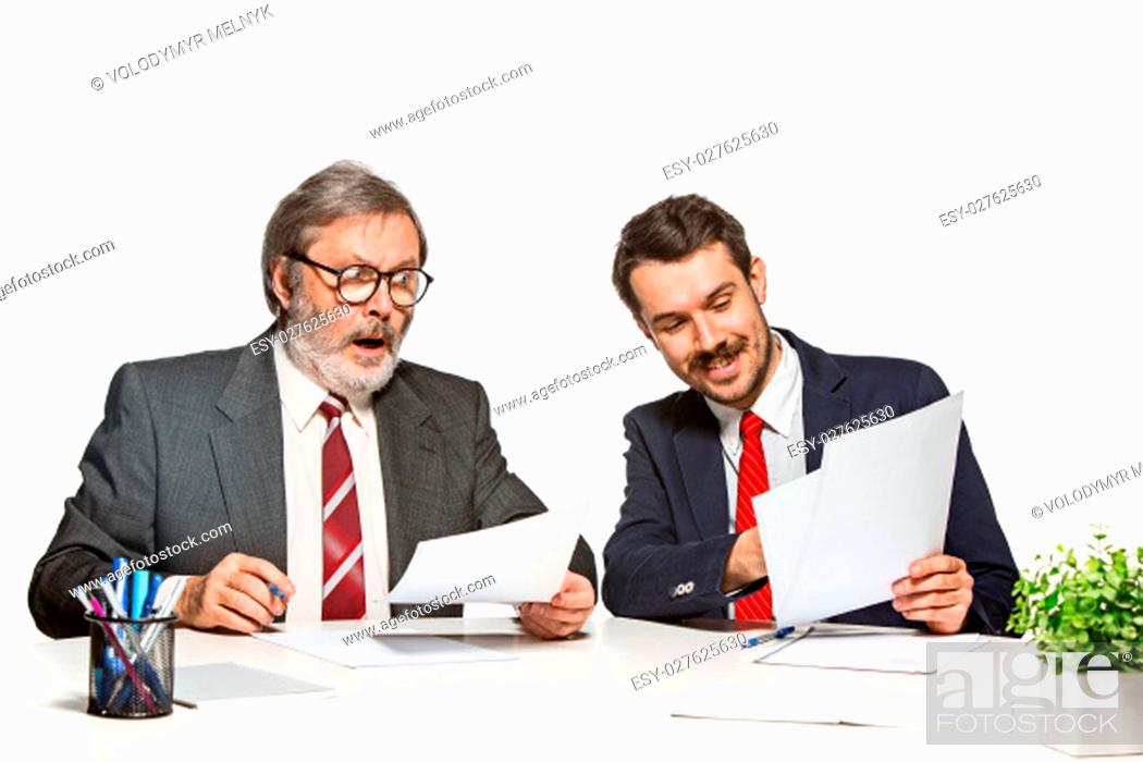 Stock Photo: The two colleagues working together at office on white studio background. They actively and emotionally discussing current plans.