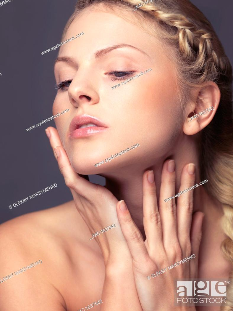 Stock Photo: Beauty portrait of a young woman touching soft skin on her face and neck.