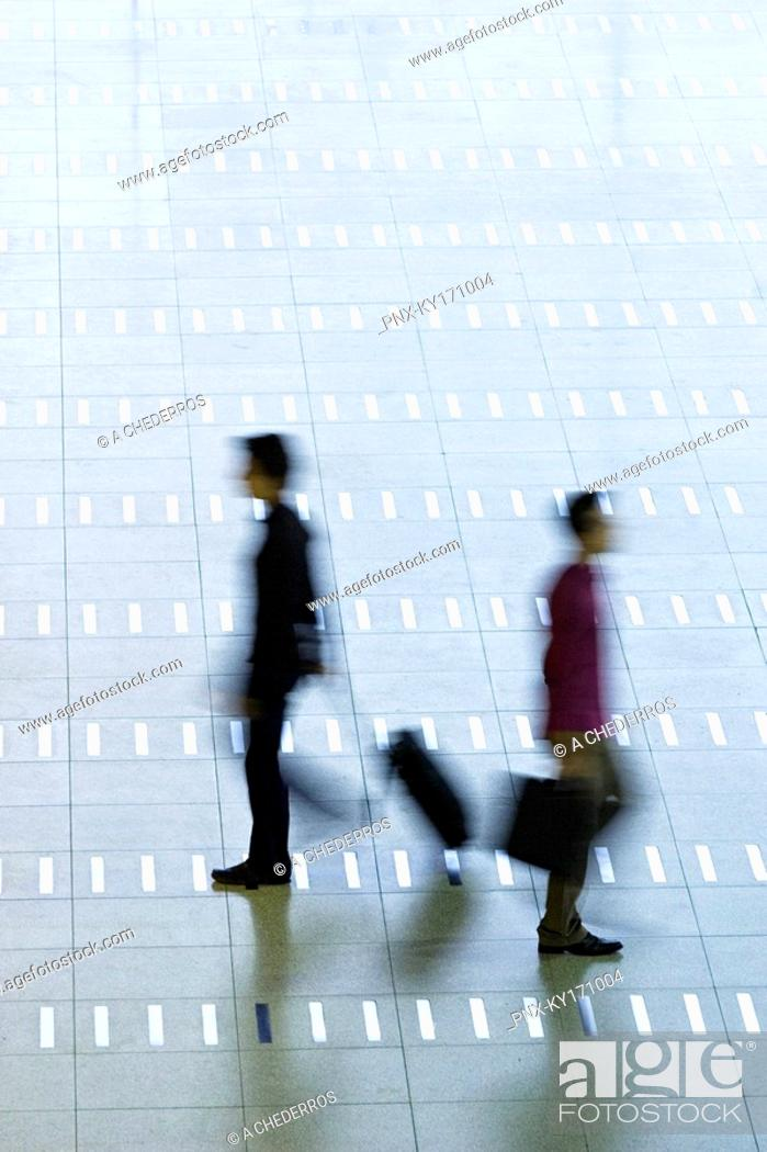 Stock Photo: High angle view of two men walking at an airport lobby.