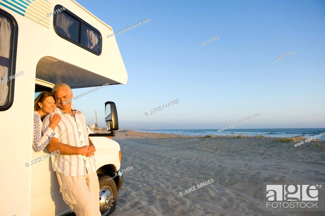 Stock Photo: Mature woman in motor home on beach embracing husband through window, smiling, portrait.