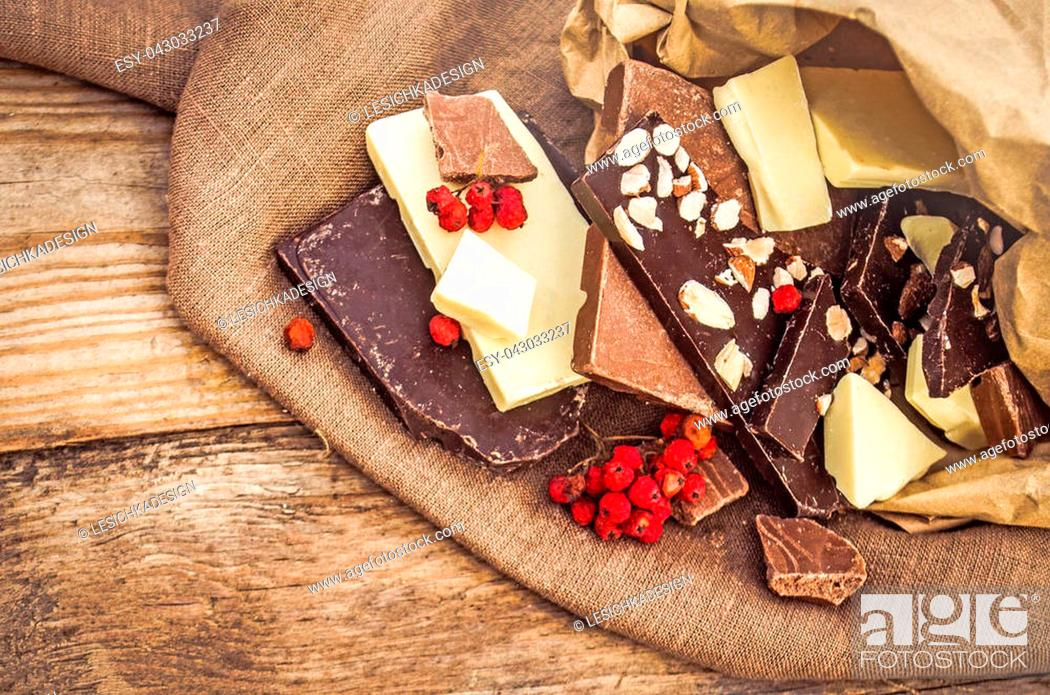 Photo de stock: hocolate mix with nuts and dried fruits on rustic wooden background. Chocolate blocks stack with different kind of chocolate. Chocolate bar pieces.