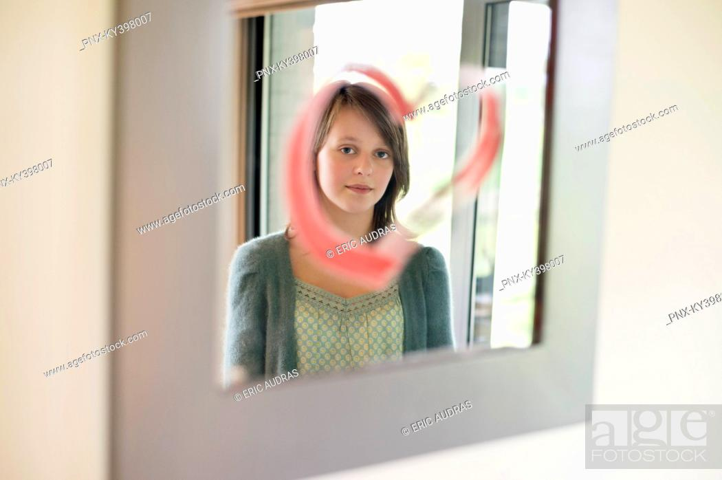 Stock Photo: Girl looking at reflection in mirror decorated with heart shape.