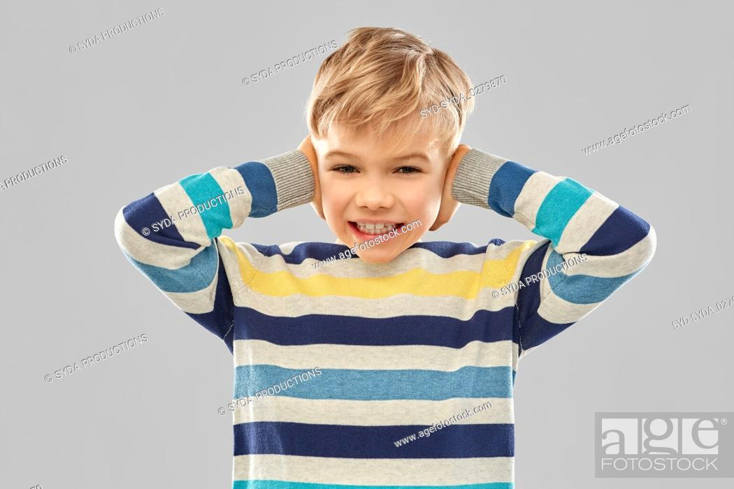 Stock Photo: stressed boy in pullover closing ears by hands.