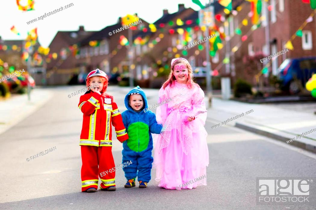 Stock Photo: Kids on Halloween trick or treat. Children in Halloween costumes with candy bags walking in decorated city neighborhood trick or treating.