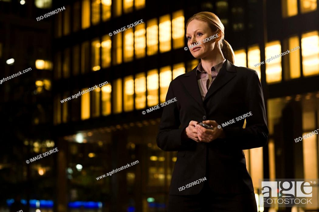 Stock Photo: Businesswoman outside an illuminated building.