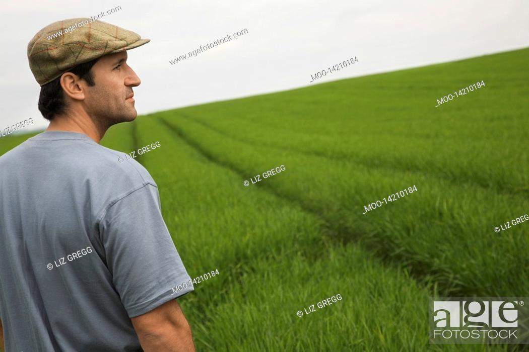Stock Photo: Man standing in field side view.