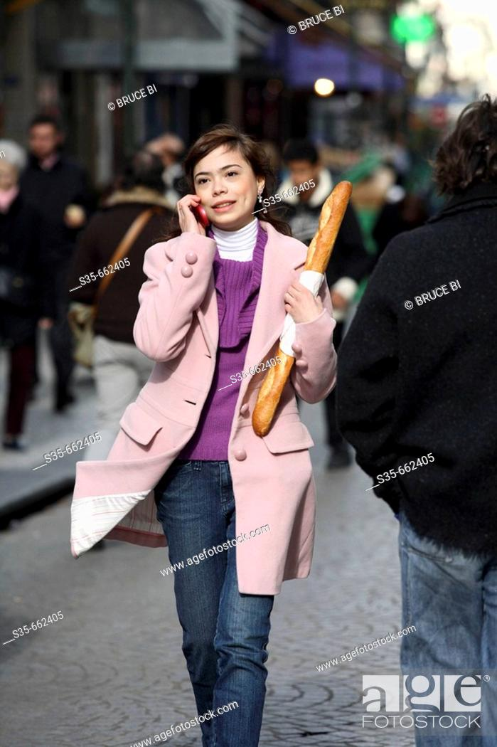 Stock Photo: A young woman holding a baguette and talking on her cell phone on the street of Paris. Paris. France.