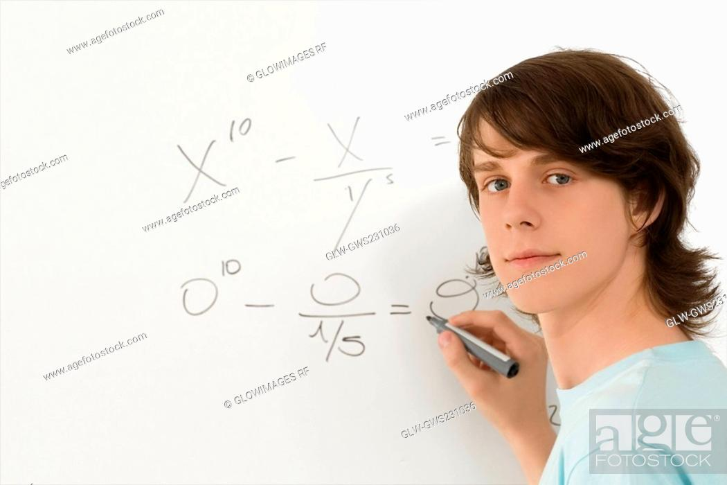 Stock Photo: Portrait of a teenage boy writing on a whiteboard.
