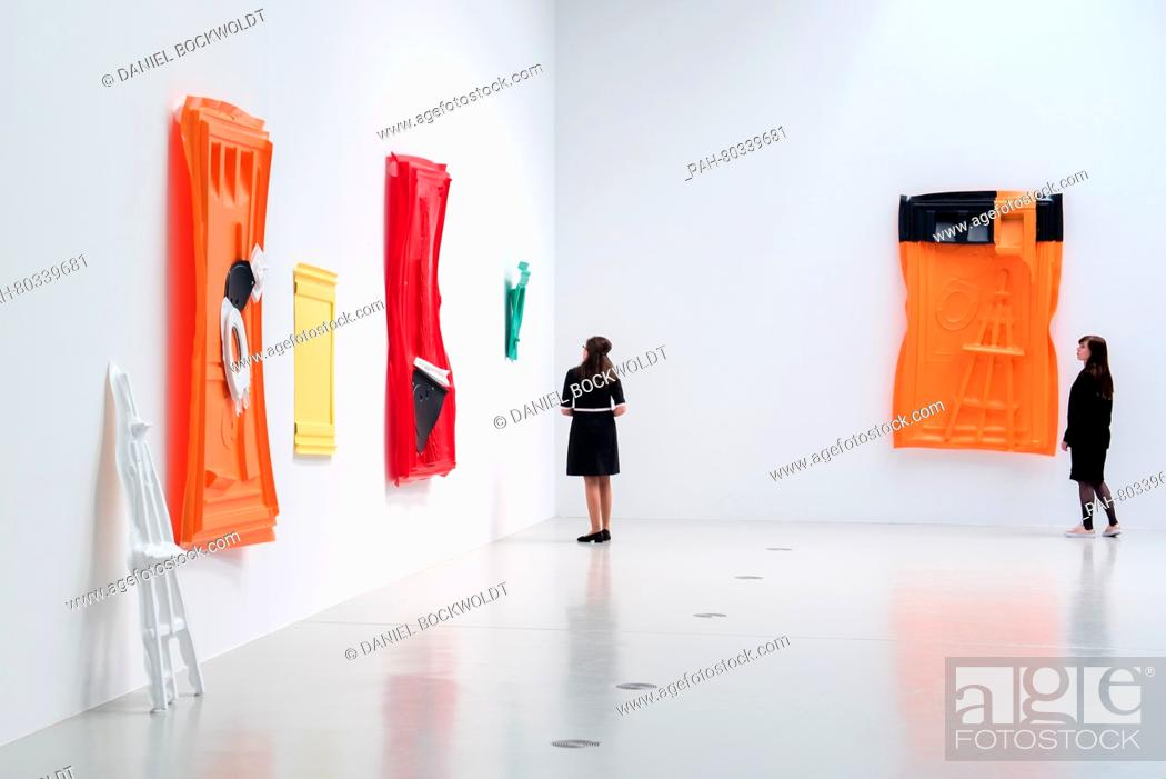 Portable Toilet Exhibition : Two women look at art works made of parts of portable toilets at an