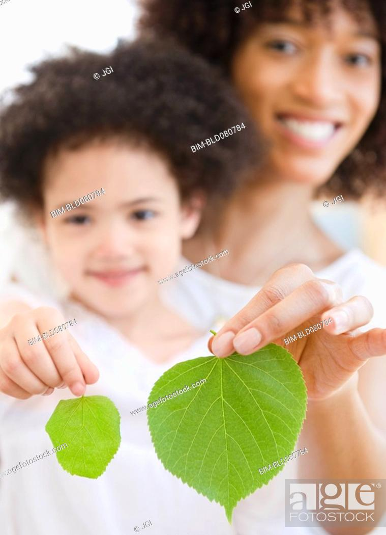 Stock Photo: Mother and daughter holding green leaves.